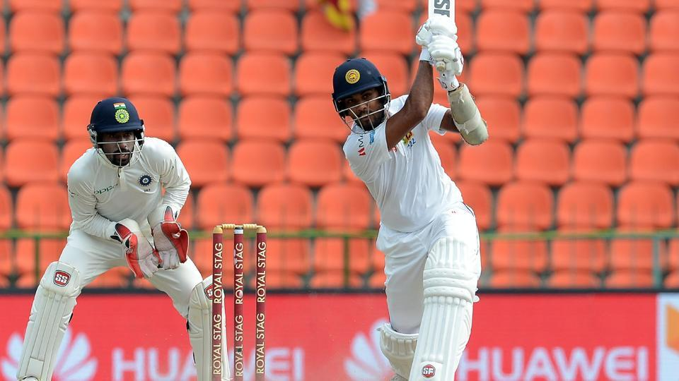 Sri Lanka cricket team skipper Dinesh Chandimal (R) is watched by Indian wicketkeeper Wriddhiman Saha as he plays a shot. (AFP)