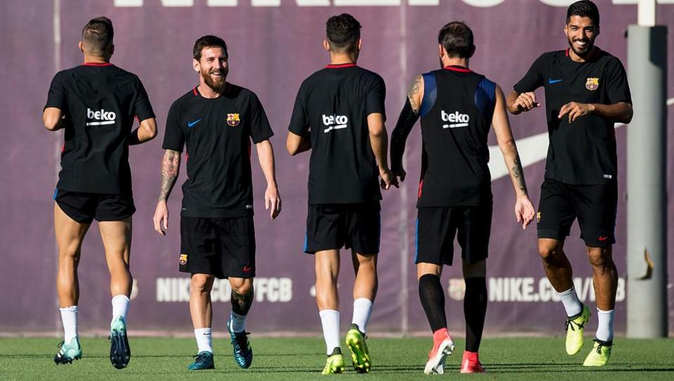 FCBarcelona forward Lionel Messi (2nd-L) Luis Suarez (1st-R) smile during a training session.