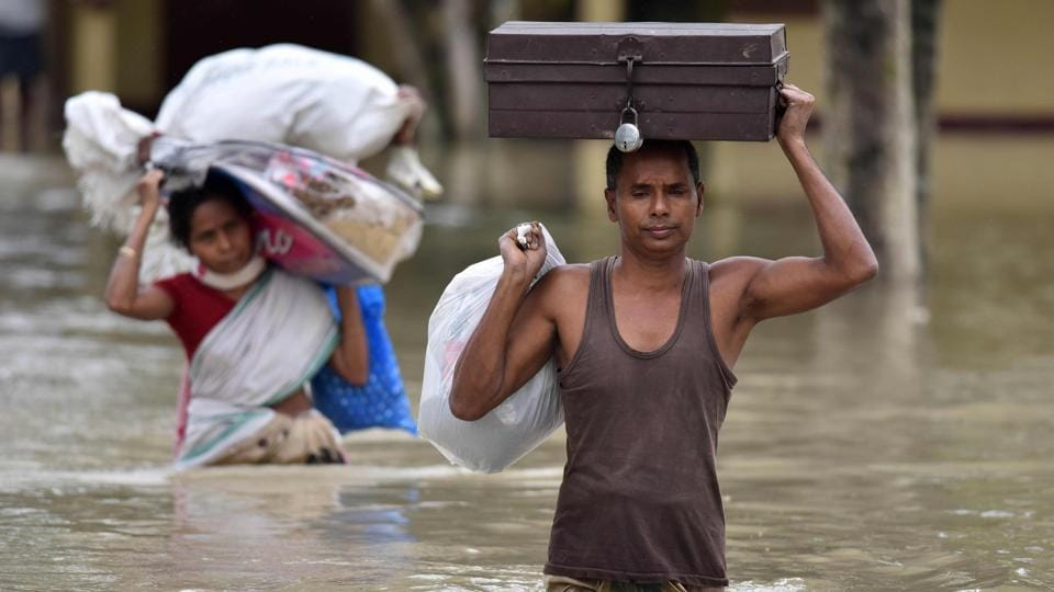 Villagers wade through flood waters while carrying household items at the flood affected Koliabor village, 186km from Guwahati, on Sunday.