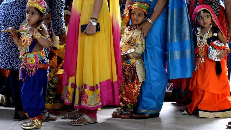 Indian children dressed as Hindu deity Krishna and his consort Radha stand in line with their mothers during an enactment competition as part of Krishna Janmashtami celebrations in Bangalore on August 12, 2017. (Manjunath Kiran/AFP)