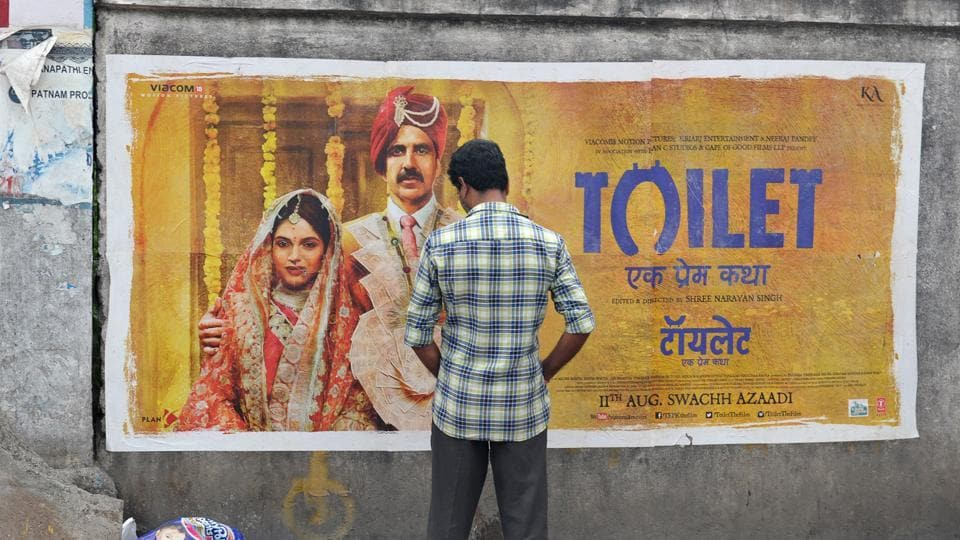 An Indian man urinates on a wall on the roadside in front of a poster for the Hindi film 'Toilet' in Hyderabad on August 12, 2017. (Noah Seelam/AFP)