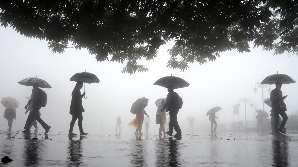 People walk with umbrellas during a rainy day on Friday morning at ridge,Shimla on Friday.  (Deepak Sansta /HT Photo)
