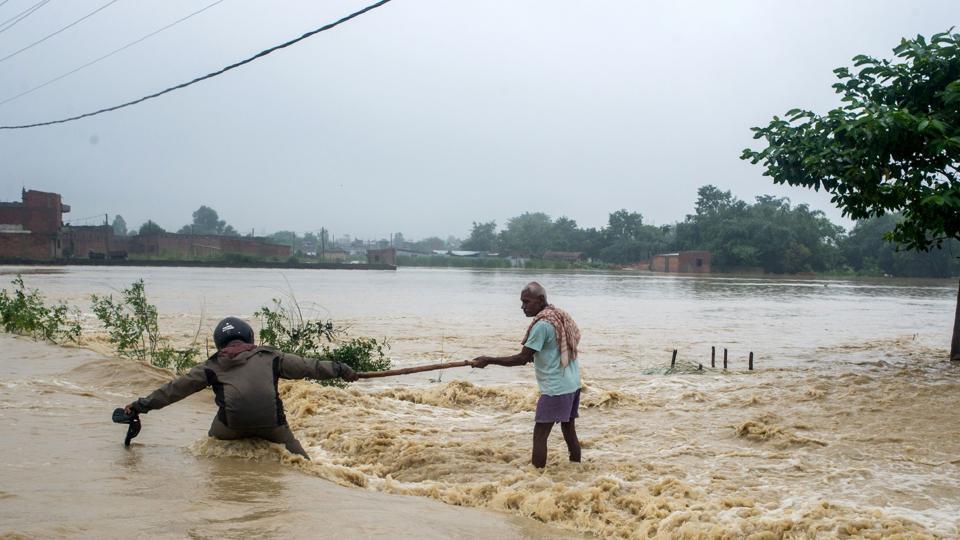 Nepali residents help each other cross a flooded road at Birgunj Parsa district, some 200km south of Kathmandu.