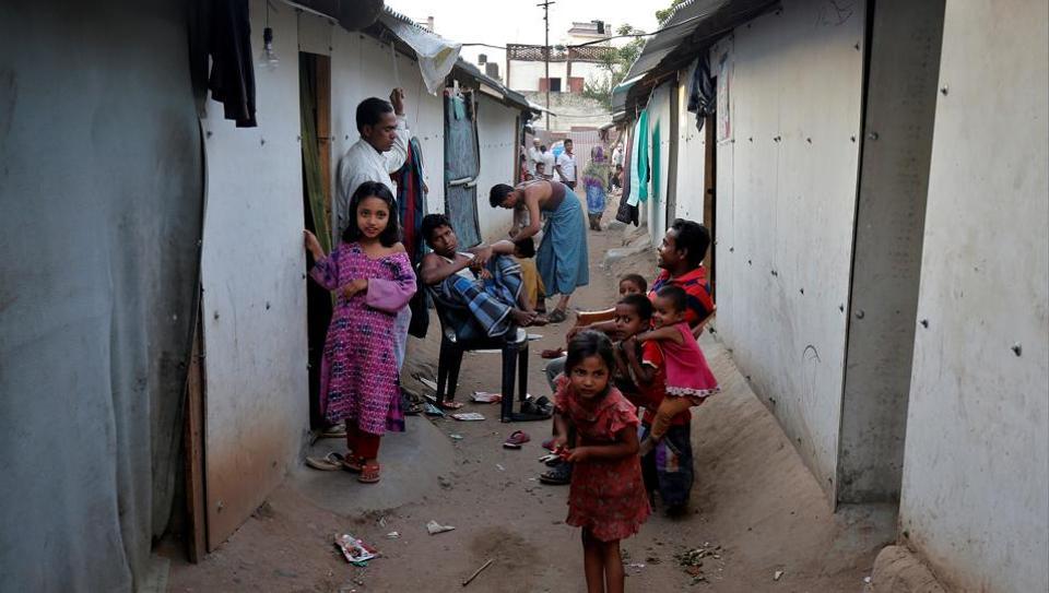 People belonging to the Rohingya Muslim community sit outside their makeshift houses near Jammu.