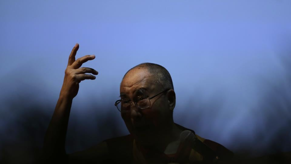 Tibetan spiritual leader the Dalai Lama gestures as he speaks on 'the art of happiness' at a public event in New Delhi on Thursday.  (Tsering Topgyal/AP)