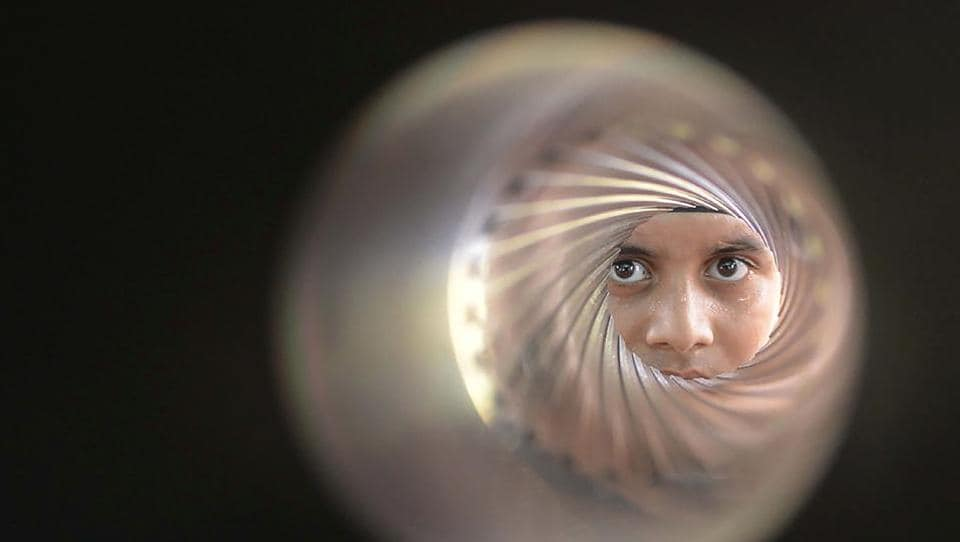 An Indian student poses as he looks down the barrel of an 84-MM rocket launcher during an Indian Army exhibition at Panther Stadium in Amritsar on August 10.  (Narinder Nanu/AFP)