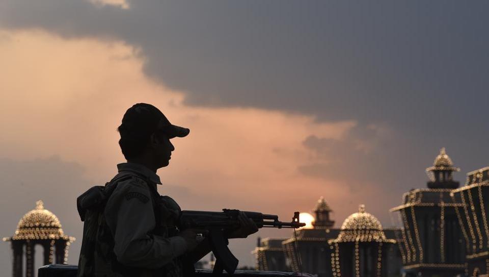 ecurity personnel stand guard around the illuminated Raisina Hill in New Delhi on Monday.