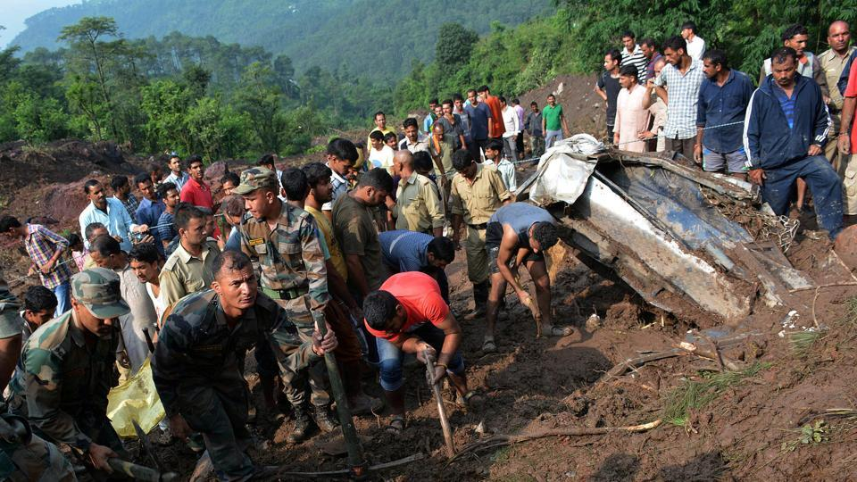 Indian army personnel and rescue workers search for survivors amid the rubble after a landslide caused by a cloudburst swept two buses off the road into a gorge, in Mandi district, in Himachal Pradesh, August 13, 2017.
