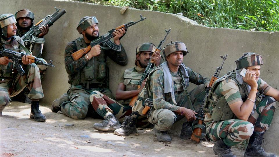 Soldiers take positions outside a house where militants were hiding during an encounter in which three Hizbul Mujahideen commanders and two soldiers were killed in Shopian district of Kashmir on Sunday.