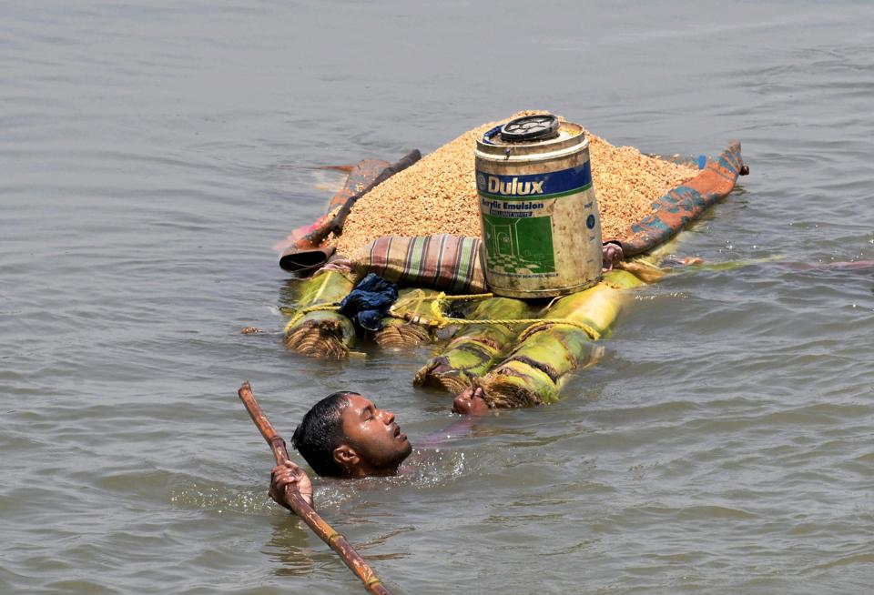 A villager carries grains on a banana raft as he shifts from a flooded village in Araria district of Bihar. Heavy rains in the last three days triggered flash floods in parts of Bihar, where 41 people have died so far, paralysing normal life and snapping rail link to the northeast from the rest of the country. (PTI)