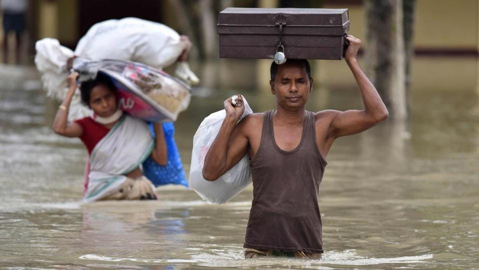 Villagers wade through flood waters carrying household items at Koliabor village in the northeastern state of Assam. Floods also affected Tripura, forcing 9,917 families to take shelter in 75 relief camps. (Biju Boro/AFP)
