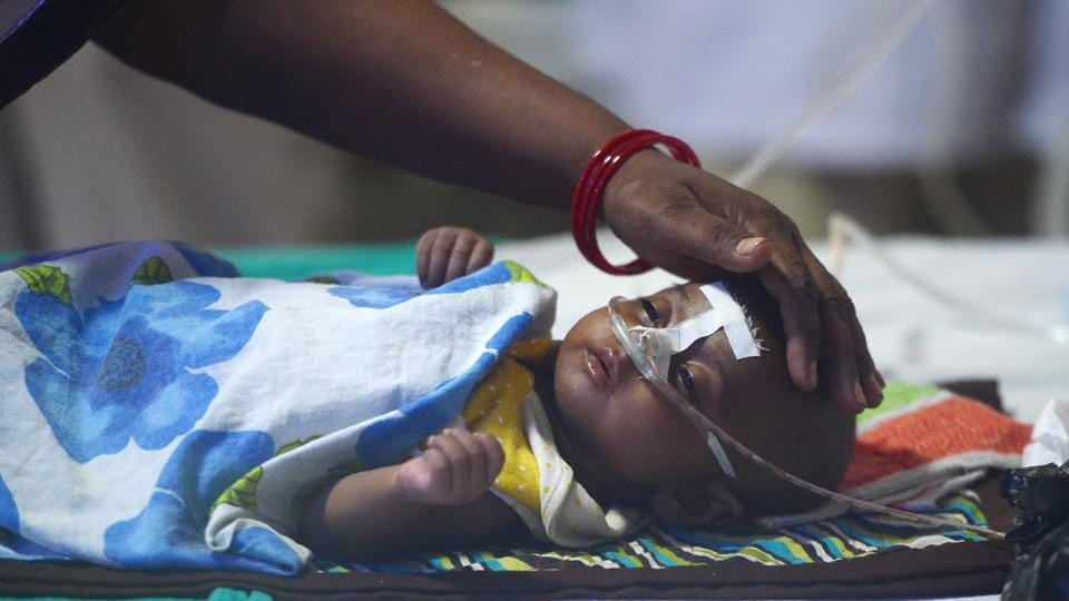 A woman looks after her child at the encephalitis ward of the Baba Raghav Das Hospital in Gorakhpur, on Monday.