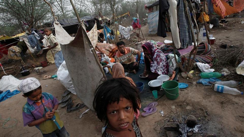 A family, who says they belong to the Burmese Rohingya Community from Myanmar, eats their breakfast at a makeshift shelter in a camp in New Delhi.