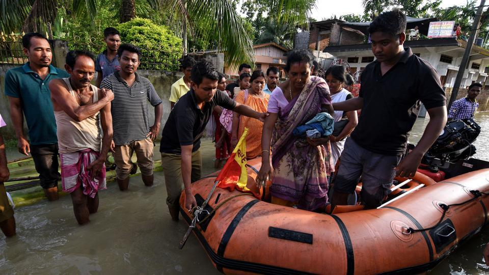 State Disaster Response Force (SDRF) personnel evacuate villagers affected by a flood in Kaliabor area in Nagaon district in Assam.