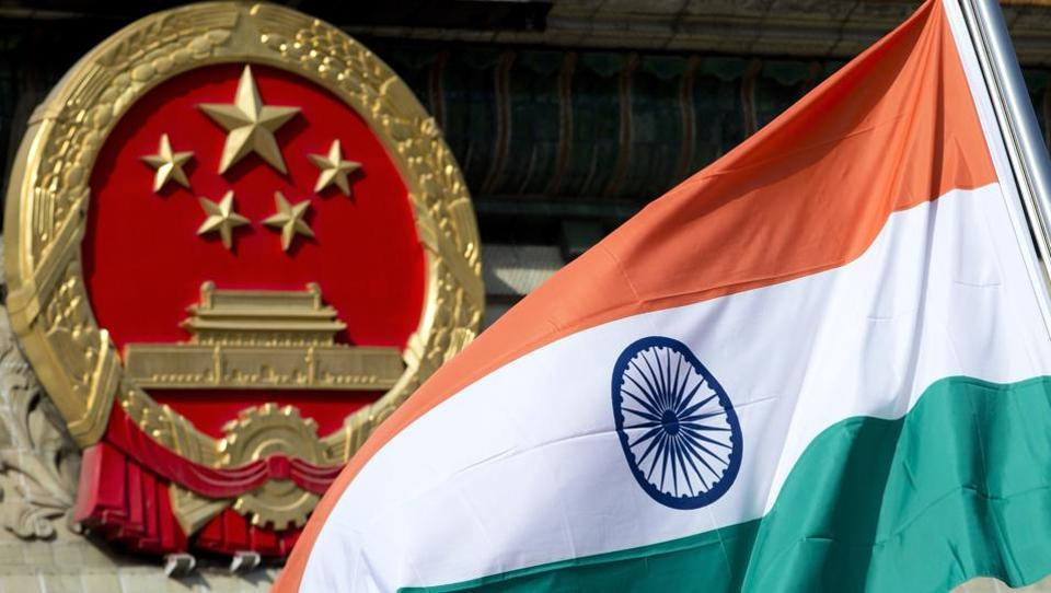 In this file photo, an Indian national flag is seen next to the Chinese national emblem during a welcome ceremony for visiting Indian officials outside the Great Hall of the People in Beijing. Tensions are running high between the two countries after China called for the immediate withdrawal of Indian troops from Doklam.