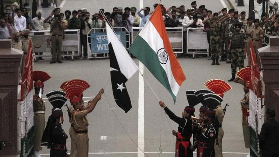 Pakistani rangers (wearing black uniforms) and Indian Border Security Force officers lower their national flags during a daily parade at the Pakistan-India joint check-post at Wagah border (File Photo)
