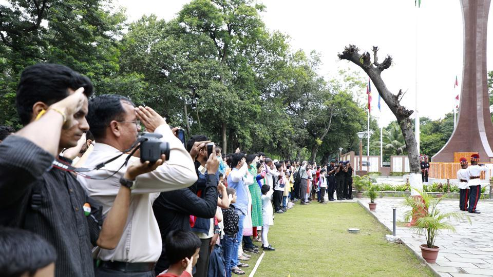 People salute at the flag hoist ceremony held at the Independence day celebration at the National War Memorial at camp  on Tuesday. (Rahul Raut/HT PHOTO)