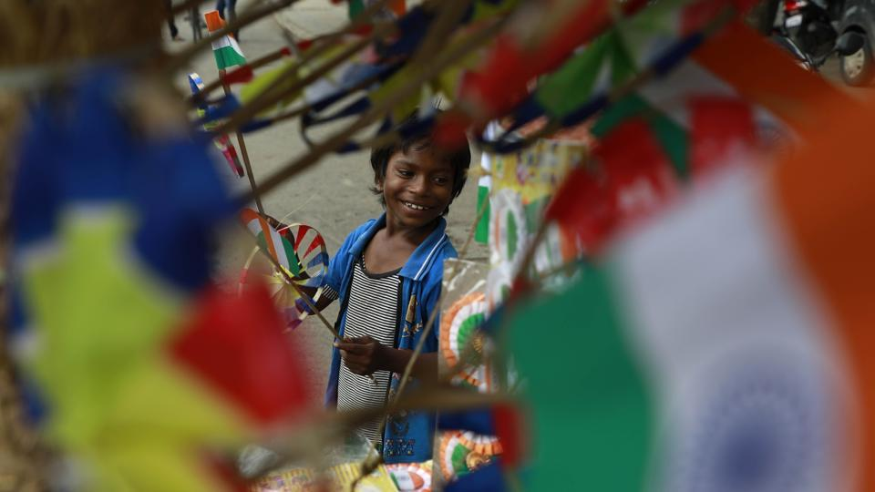A boy sells national flags at Satara road, in Pune, on Monday, August 14, 2017.  (Rahul Raut/HT PHOTO)