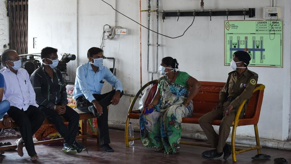 A security guard and relatives of a Swine flu (H1 N1) patient interact outside the isolation ward of the Ahmedabad Civil Hospital, in Ahmedabad on August 12, 2017.