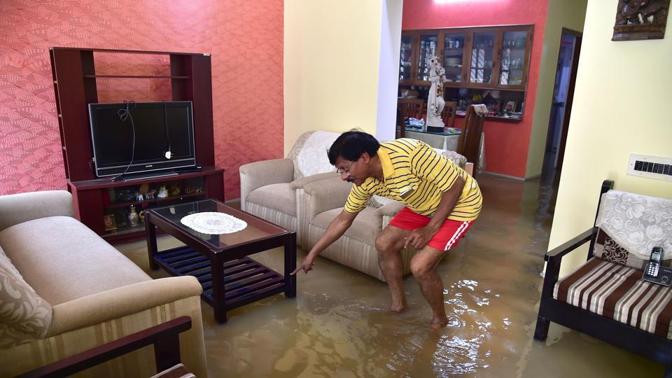 An Indian resident looks for a lost item in his flooded house situated in a low lying area in Bengaluru on August 15, 2017.