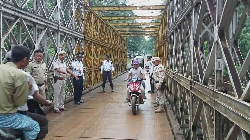 Indian and Myanmar policemen guide people from the neighbouring country to drive on the left side of the road as they enter Moreh in Manipur through the 'friendship bridge'.