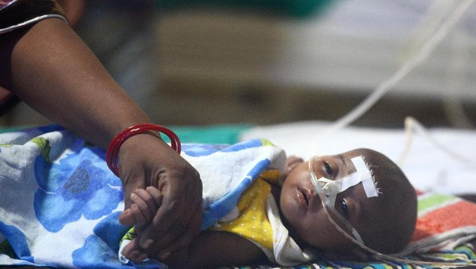 A woman holds her child's hand at the encephalitis ward of the Baba Raghav Das Hospital in Gorakhpur, Uttar Pradesh.