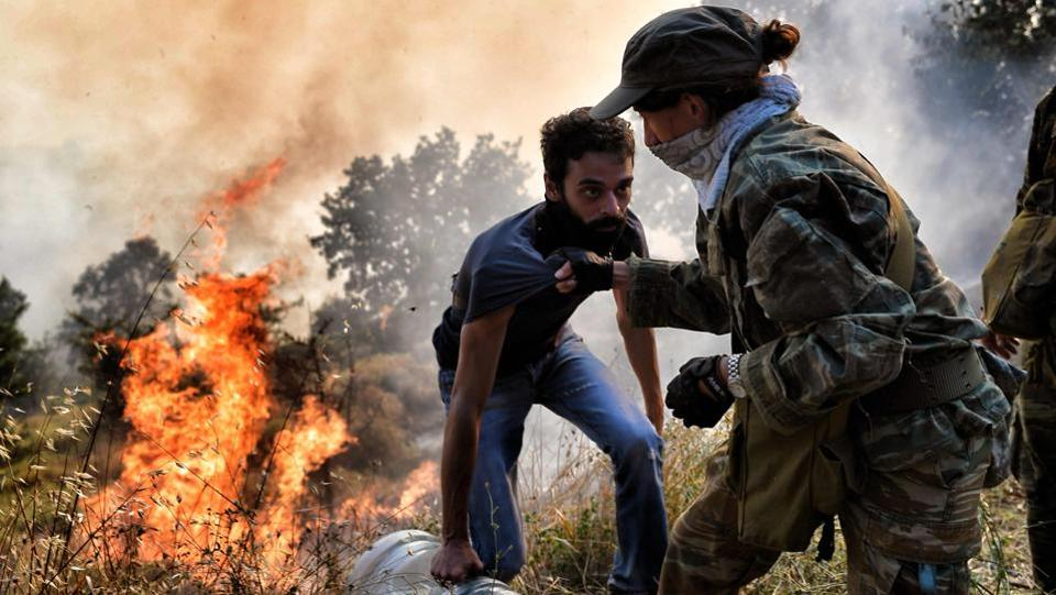 Firemen, army personnel and volunteers work to extinguish a fire east of the Greek capital Athens on August 15, 2017. The army was called in to assist firefighters around Kalamos, setting up bulldozers as firebreaks around the area. (Aris Messinis / AFP)