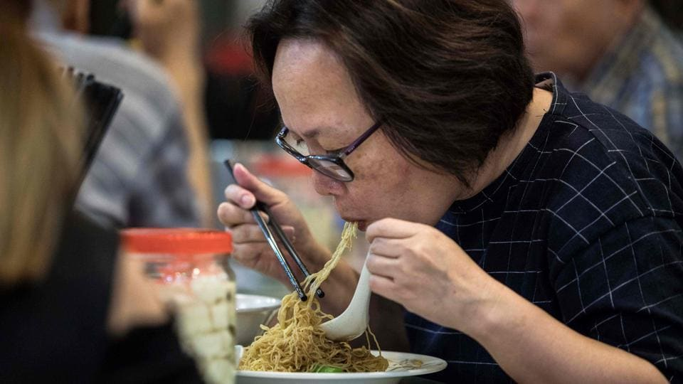 A woman eats noodles, handmade using a traditional bamboo pole technique, at a restaurant in Hong Kong.