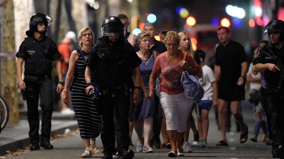 Policemen accompany people outside a cordoned off area after a van ploughed into the crowd, killing at least 12 people and injuring over 80 on the Rambla in Barcelona on August 17, 2017.