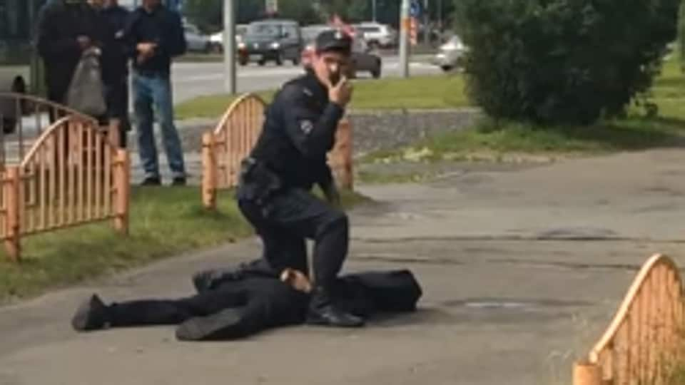 Screengrab of a video showing a police official with the killed assailant in Russia's Surgut on Saturday.