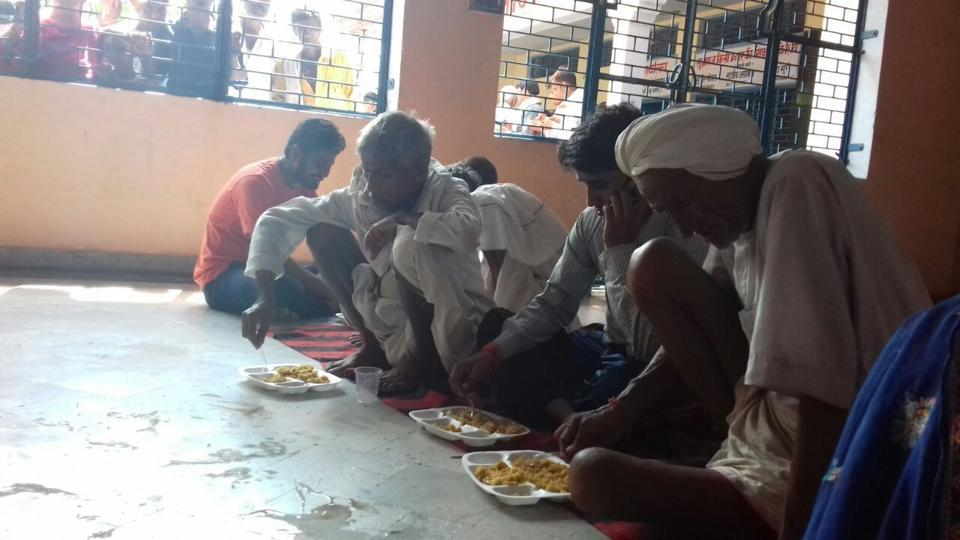 Survivors of the Utkal Express train accident eating lunch at Sri Jharkhand Mahadev Mandir in Khatauli.