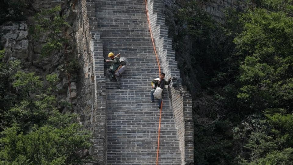 Workers carry their tools and belongings as they climb down the Jiankou section of the Great Wall, located in Huairou District, north of Beijing, China, June 7, 2017.