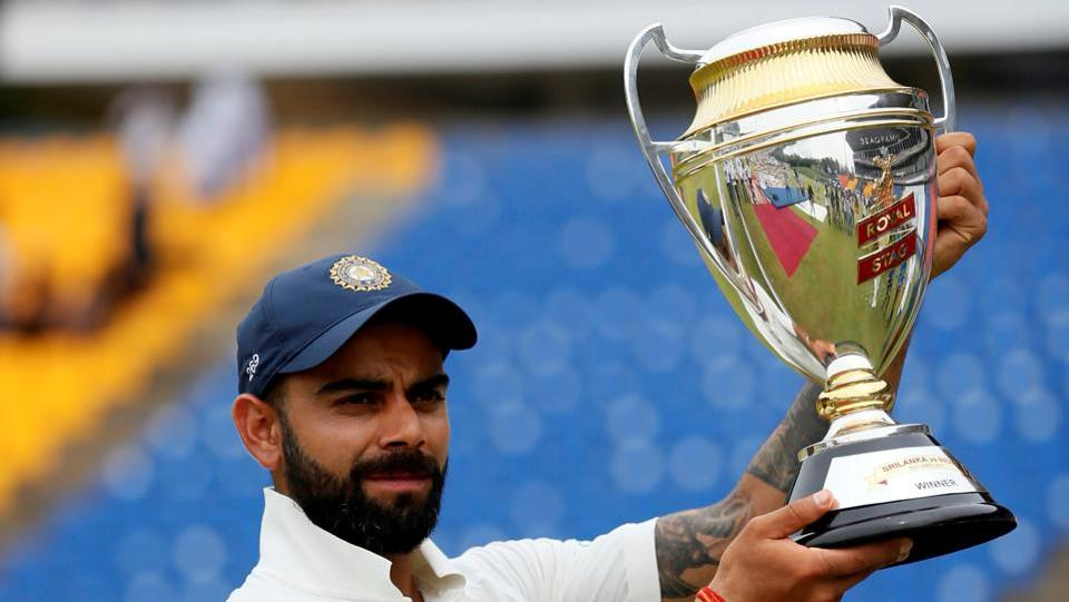 Virat Kohli holds the trophy for photographs after they won the match and test cricket series against Sri Lanka. (Dinuka Liyanawatte/REUTERS)