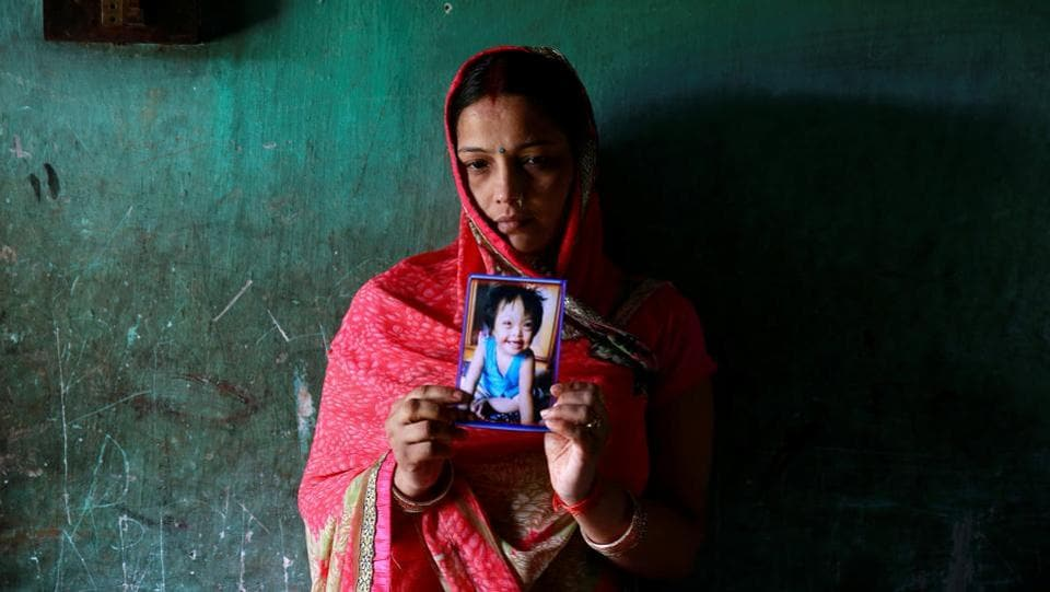 Rinki Singh, 31, holds a photo of her daughter Aarushi, 6, who died in the intensive care unit (ICU) of the Baba Raghav Das hospital in the Gorakhpur district on August 14. (Cathal McNaughton/REUTERS)