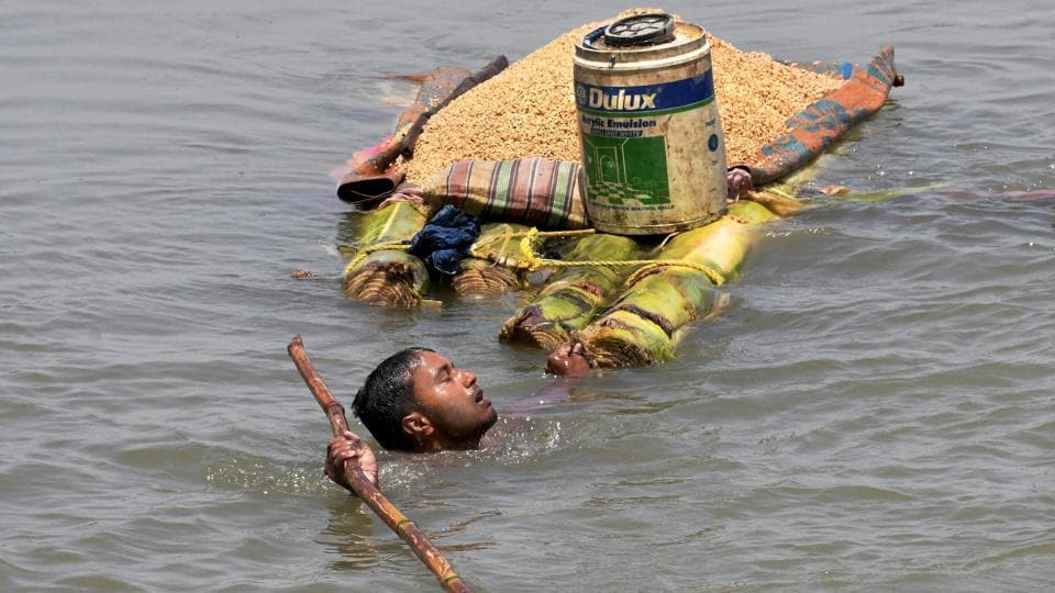 A villager carries grains on a banana raft as he shifts from a flooded village in Araria district of Bihar on Monday. (PTI)