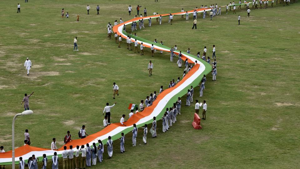 School children hold a thousand feet long National flag organized by consumer rights organization at Noida stadium, in Noida on Monday. (Virendra Singh Gosain/HT PHOTO)
