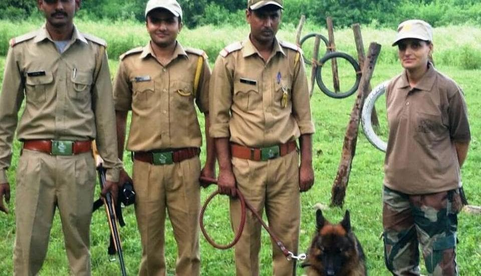 Forest guards with their sniffer dog ahead of a training session.