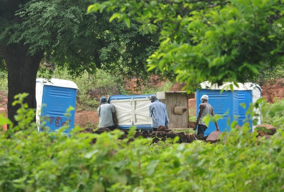 A team of Bhopal Municipal corporation putting up community toilet near house of Kamal Singh Uike where BJP president Amit Shah had lunch on Sunday, in Sewania Gond near Suraj Nagar in Bhopal, India, on Monday, August 21, 2017.
