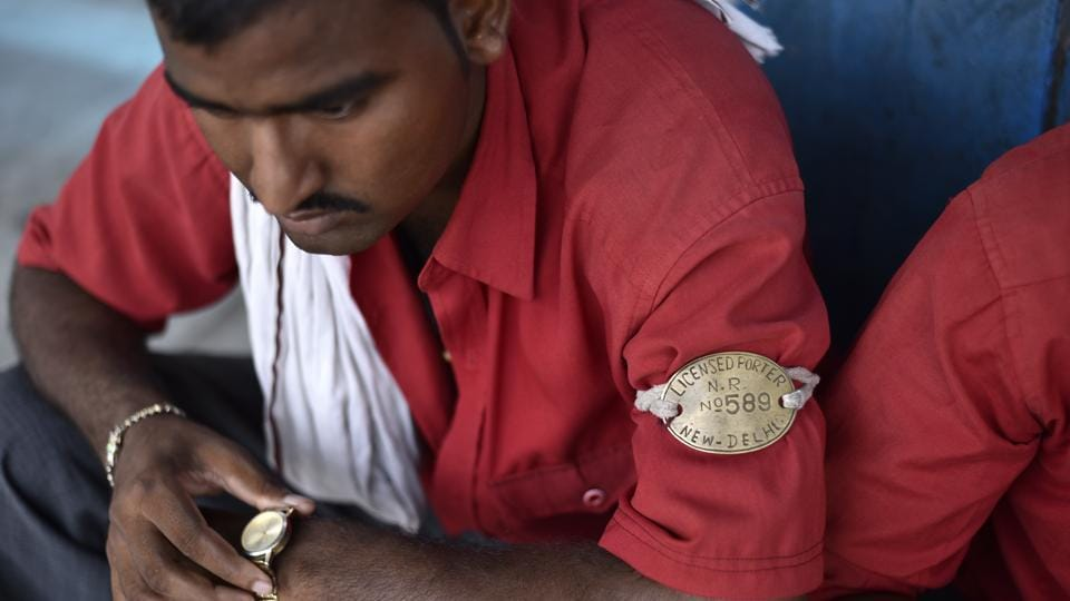 The coolie or train porter in his bright red shirt and copper armband has been ubiquitous at Indian railway stations ferrying luggage to and from trains – even glamorised in cinema courtesy Amitabh Bachchan. Once the go-to option for passengers looking for quick passage through platforms, newer infrastructure facilities for the aid of commuters have greatly reduced dependence on these porters. Their concerns are compounded by demands for better working conditions and occupational perks. (Burhaan Kinu / HT Photo)