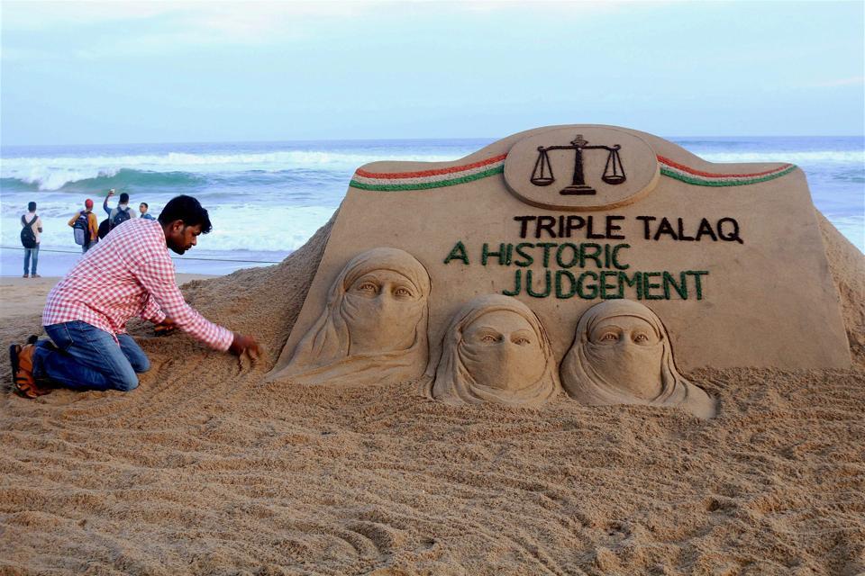 "Sand artist Sudarsan Pattnaik makes a sand sculpture carrying the message ""Triple Talaq A Historic Judgement"" at Puri beach of Odisha on Tuesday."