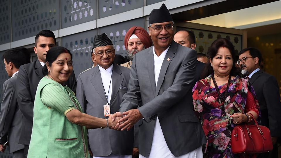 Foreign minister Sushma Swaraj (L) shakes hand with Nepal's Prime Minister Sher Bahadur Deuba (C) at Indira Gandhi International Airport in New Delhi on Wednesday.