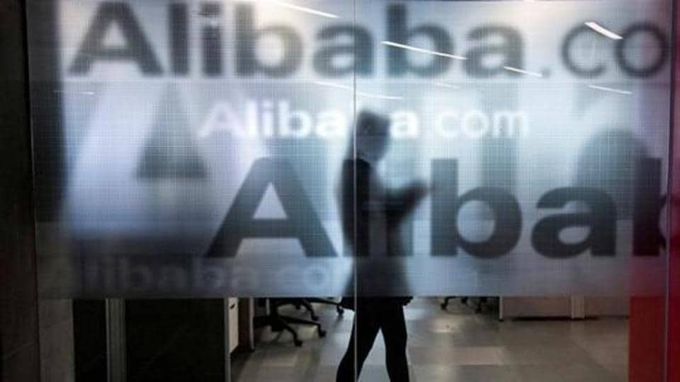 An employee is seen behind a glass wall with the logo of Alibaba at the company's headquarters on the outskirts of Hangzhou, Zhejiang province in China.
