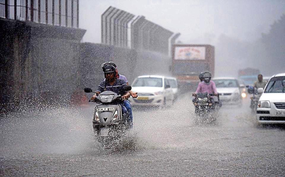 People caught in the Monsoon rain near Moti Bagh in New Delhi, India, on Wednesday.