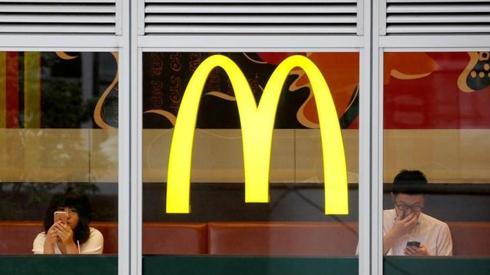 Customers using mobile phones are seen through the windows of a McDonald's store in Tokyo, Japan July 22, 2016.