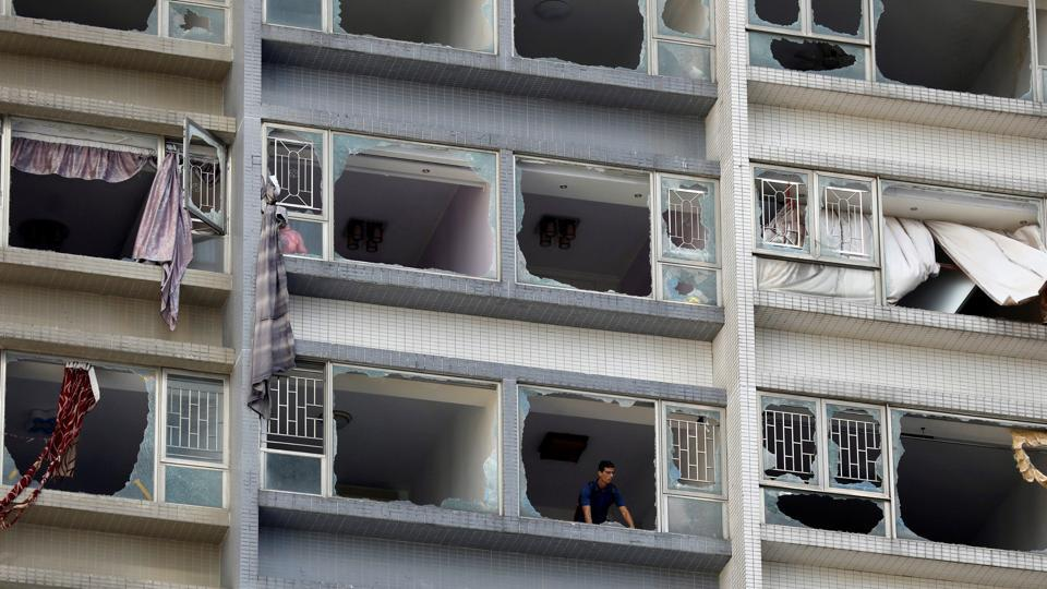 A man looks out from inside an apartment building through broken windows shattered by Typhoon Hato in Macau. The most powerful typhoon to hit the southern Chinese region in more than half a century bludgeoning into the city with winds of up to 200 kilometers per hour. (Tyrone Siu / REUTERS)