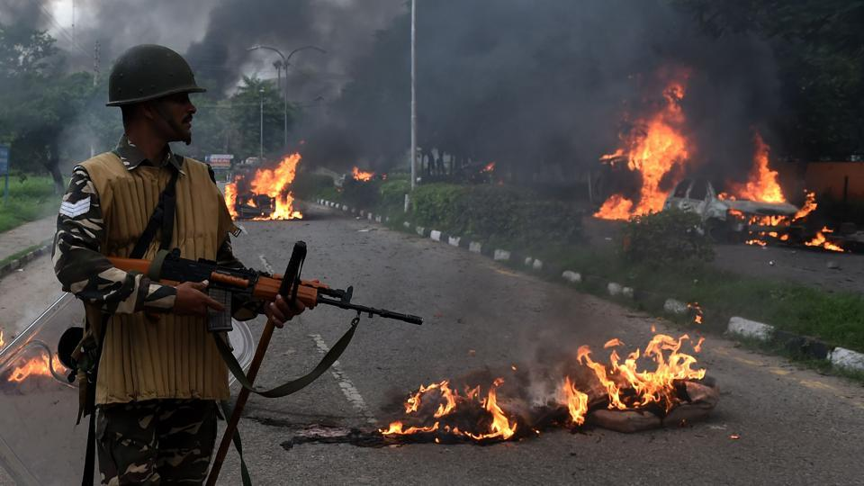 A security personnel looks at burning vehicles set alight by rioting followers of Gurmeet Ram Rahim Singh, who was convicted of rape, in Panchkula.