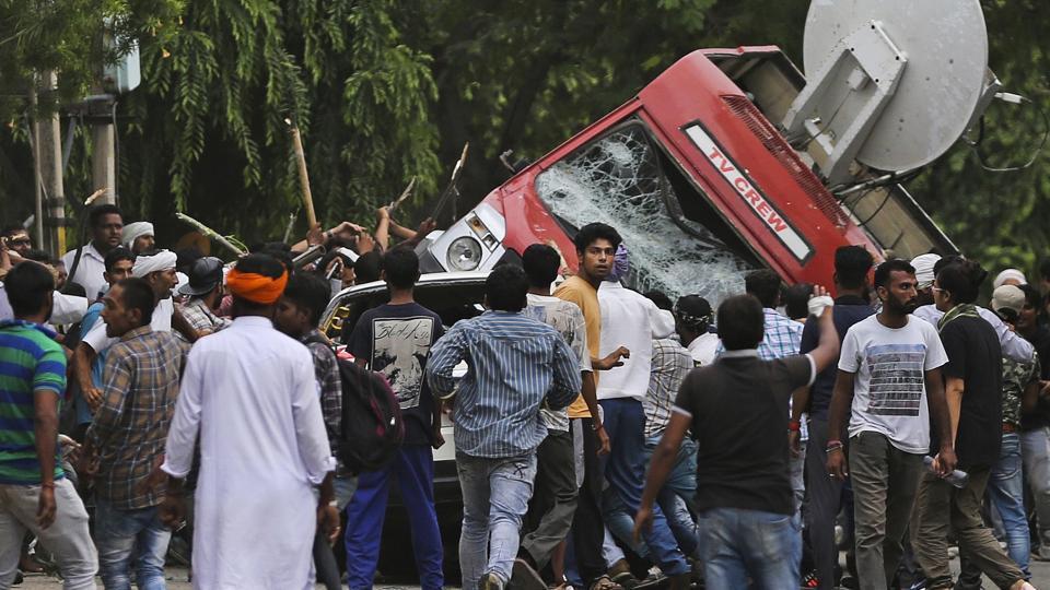 Dera Sacha Sauda supporters overturn an OB van on the streets of Panchkula.