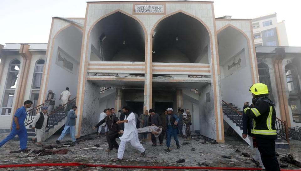 Afghan men carry a dead body from the site of a suicide attack followed by a clash between Afghan forces and insurgents after an attack on a Shi'ite Muslim mosque in Kabul, Afghanistan, August 25, 2017.