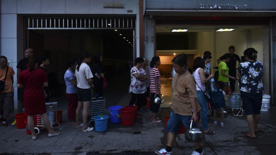 Authorities have struggled to restore order in the city of 600,000, with some residents having to queue for water from fire hydrants. According to Xinhua, almost 2 million households lost power temporarily while fishing boats were called back to port with train services and flights suspended. (Anthony Wallace/ AFP)