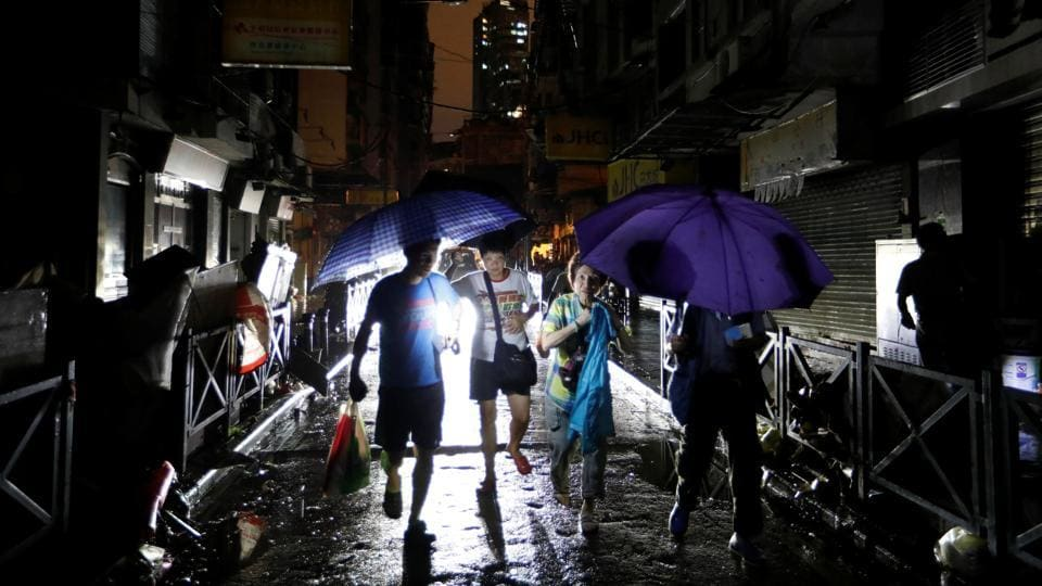 People walk on a street during a power outage after Typhoon Hato hit in Macau. Macau has rapidly transformed since 1999 into a gambling hub many times larger than Las Vegas, with major U.S. casinos piling in. Infrastructure, however, has mostly failed to keep pace with this expansion despite the rise of a wave of glitzy new casino resorts. (Tyrone Siu / REUTERS)